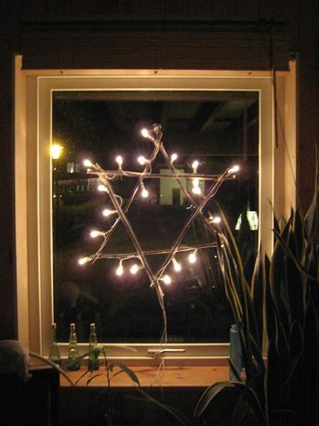 Stern aus �sten, mit Lichterkette best�ckt, im Fenster h�ngend